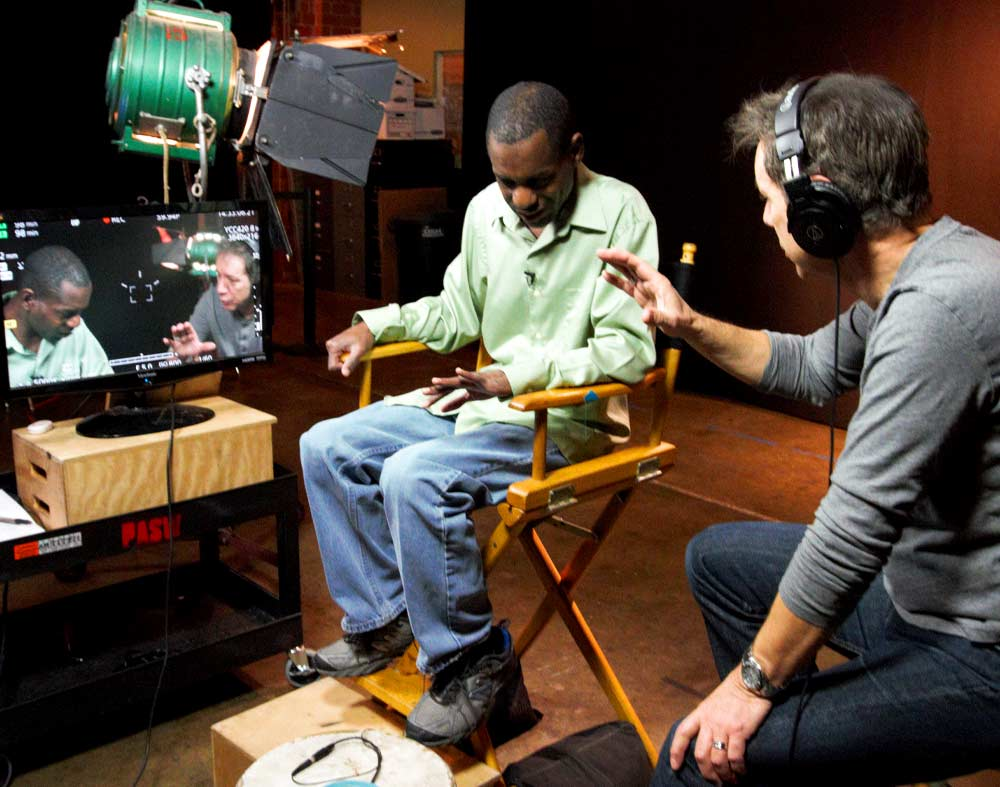 A white man wearing headphones gives direction to a Black actor who is sitting in a chair wearing a green shirt and looking down. Their faces are captured on a monitor next to the actor, and lighting equipment is in the background.