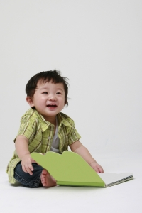 A photo of a toddler playing with a green file folder