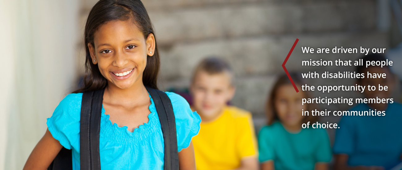 Young female student wearing backpack at school.