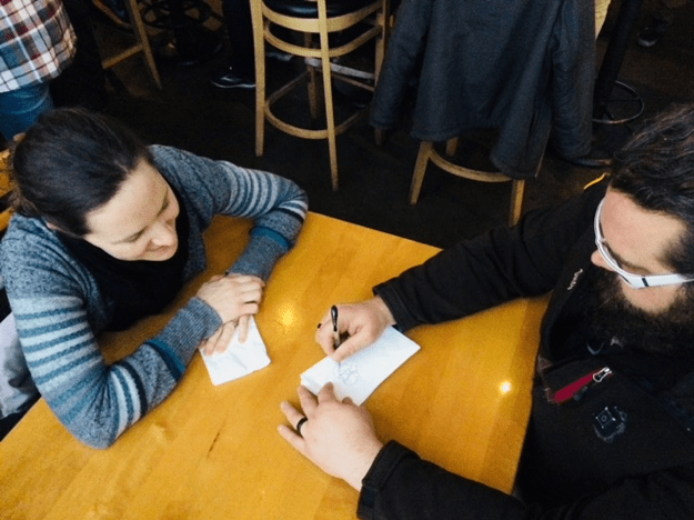 Katie Thune and her husband, Dusty, sitting at a restaurant table. Dusty is sketching on a piece of paper.