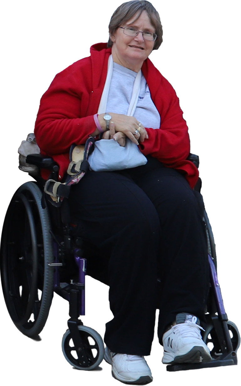 """A photo of Patty Goss, who tells her personal story in """"There's a Better Way to Live: Reflections of a Self-Advocate."""" She's sitting in her wheelchair, looking at the camera and smiling. This image has been cut out of a larger photo and shows only her against a white background."""