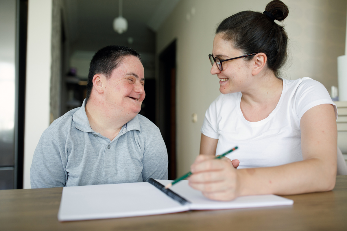 "The photo across the top of the first page of the article ""Supported Decision-Making: U.S. Status and Trends"" shows a man with Down syndrome sitting at a table next to a woman who is assisting him with a task. They are both smiling and looking at each other, and in front of them on the table is an open notebook. The woman is holding a pencil as they talk."
