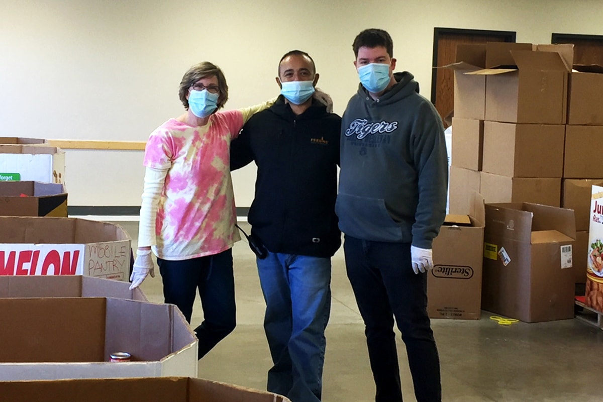 A woman and two men stand with arms around each other in a room with packing material and a stack of cardboard boxes behind them. The woman has short hair and is wearing a mask, a pink and yellow tie-dyed shirt, and plastic gloves. The main in the middle wears a mask, dark sweatshirt, and jeans. The main on the right wears a pullover hoodie with Tigers on the front, jeans, and a mask.