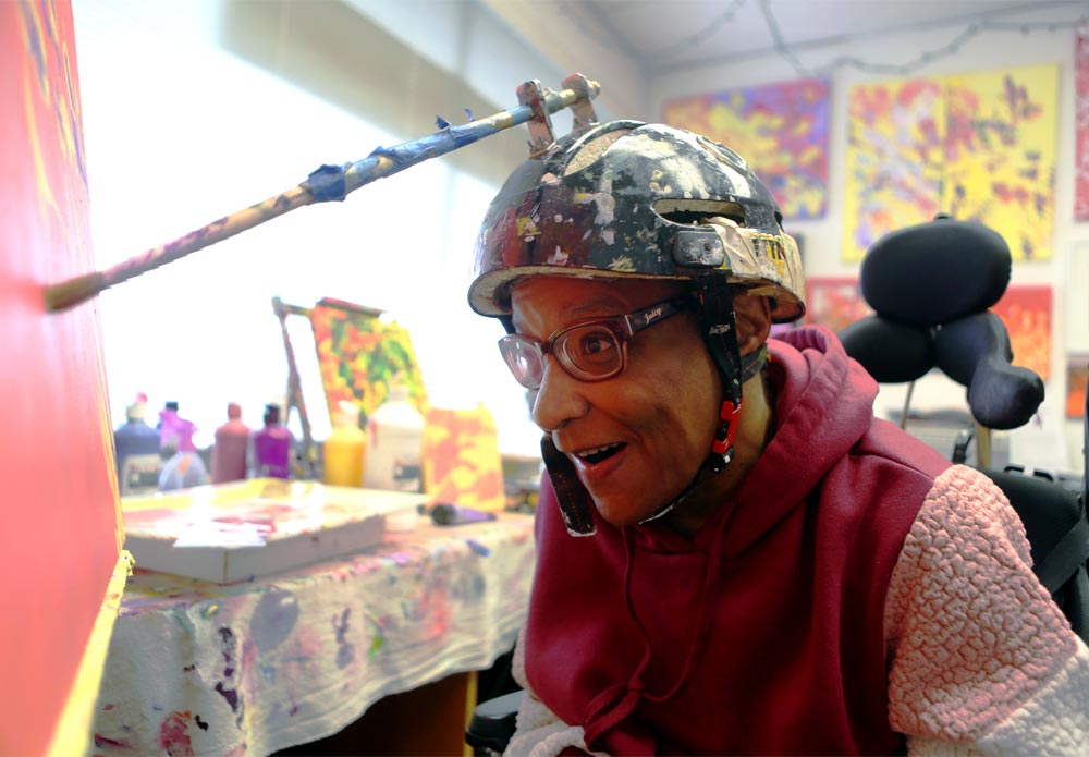 A woman with glasses wears a helmet that has a paint brush attached to it as she paints on canvas. Her mouth is open and she is smiling as she concentrates on the painting. She is wearing a dark pink jacket and several colorful paintings and art supplies are in the background.