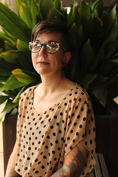 Nick Winges-Yanez sitting in front of a green plant, short brown hair, glasses, wearing poka-dot print top