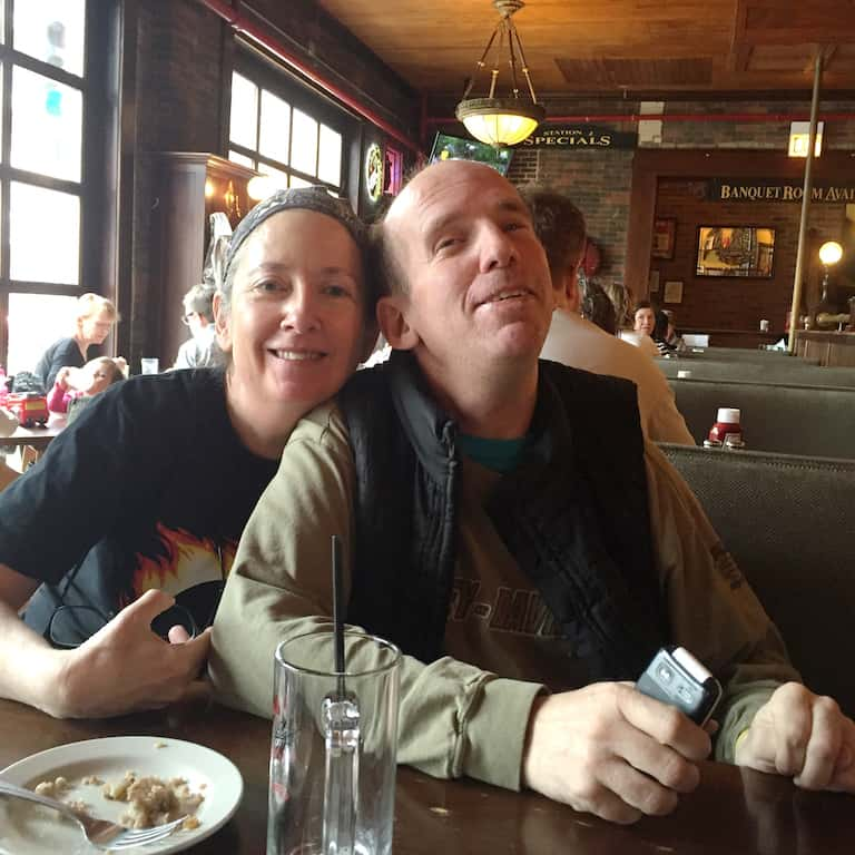 The author, Nora, sits in a cafe after a casual meal with her brother Patrick. Both are looking at the camera and smiling. Patrick wears a vest and green shirt. Nora is wearing a head covering and a black t-shirt, and leans into her brother's shoulder.