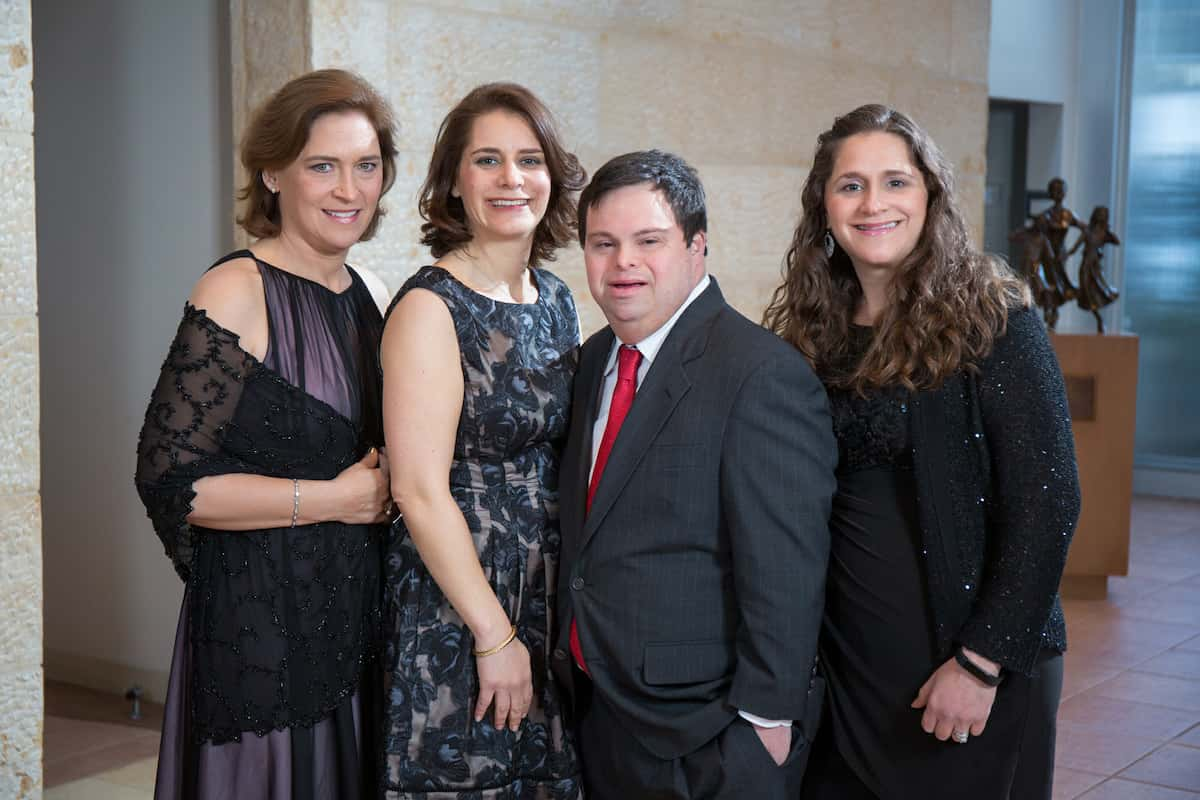 The four siblings as adults, attending a family celebration in 2018. The sisters are wearing dresses and Evan wears a dark suit with a red tie.