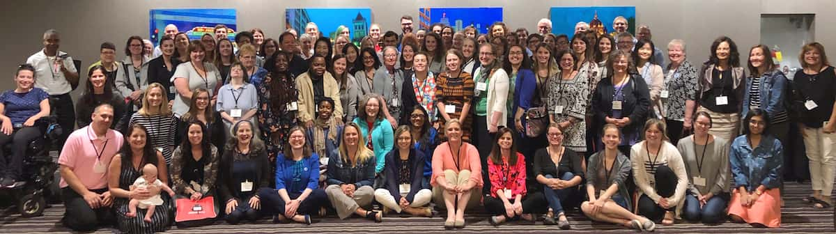 A group of more than 50 participants at a 2019 Sibling Leadership Network conference stand in rows for a posed photograph. Front-row participants kneel or sit crossed-legged, one holds an infant. Everyone is smiling.