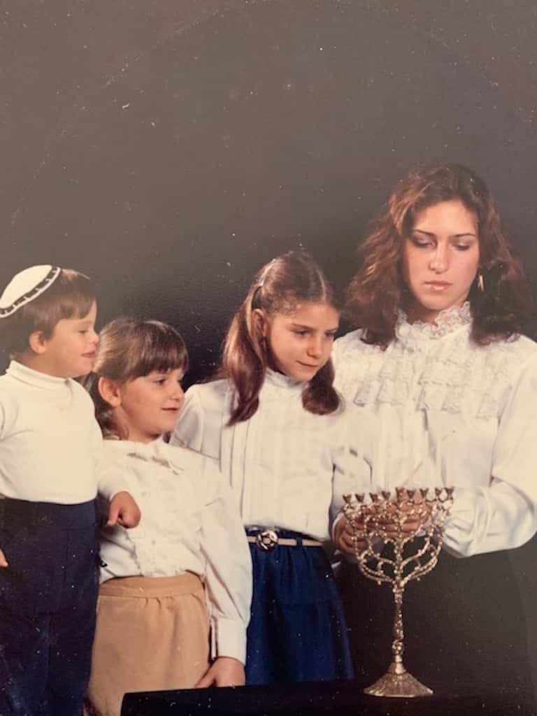 Nodvin family siblings Evan, Mindee, and Michelle gather around Alison as she lights a menorah in 1982 when they were children. A young Evan stands on a chair to see what's going on.