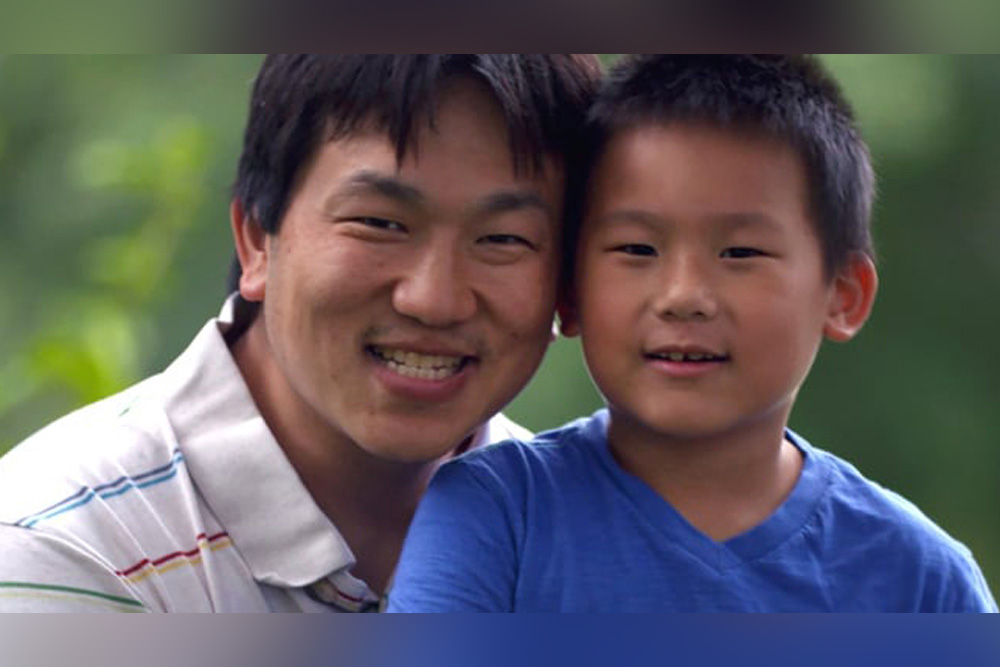 Asian man with his son. Both are smiling.