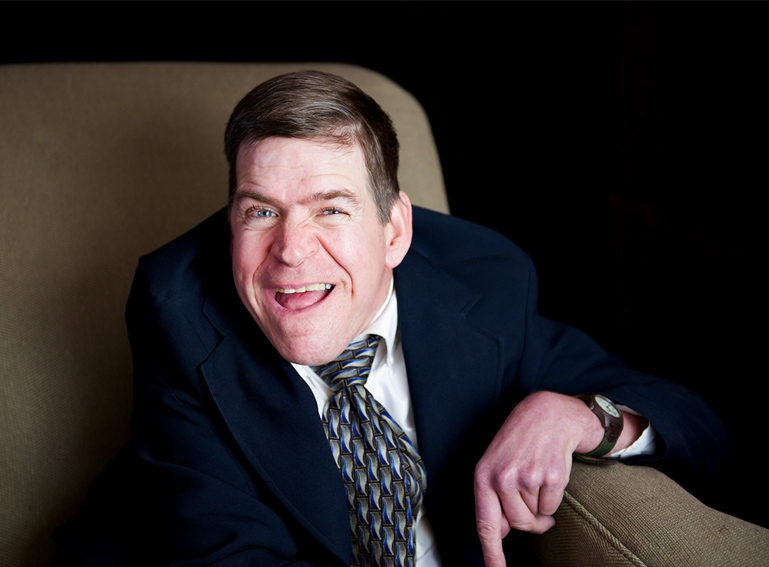 "A close-up photo of John Smith, author of the first of the four visions of self-determination in the article ""The Future of Self-Determination: Four Visions."" He is wearing a suit and tie, sitting in a big recliner-type chair, looking at the camera and smiling."