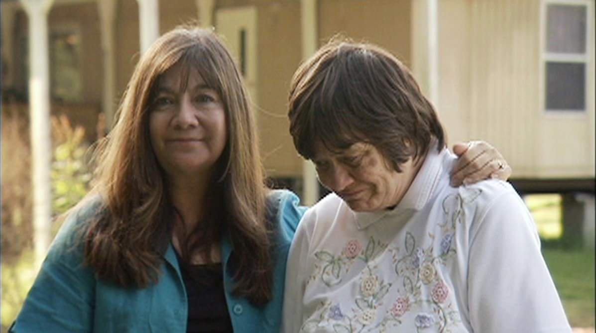 A white woman with long brown hair has her arm around another white woman with short brown hair. The woman with long hair wears a turquoise top and smiles slightly. The other woman looks down.