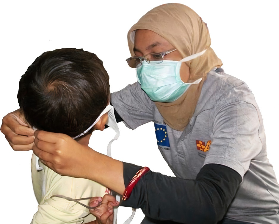 A woman wearing a beige headscarf and glasses helps a young child with his back to the camera put on a face mask.