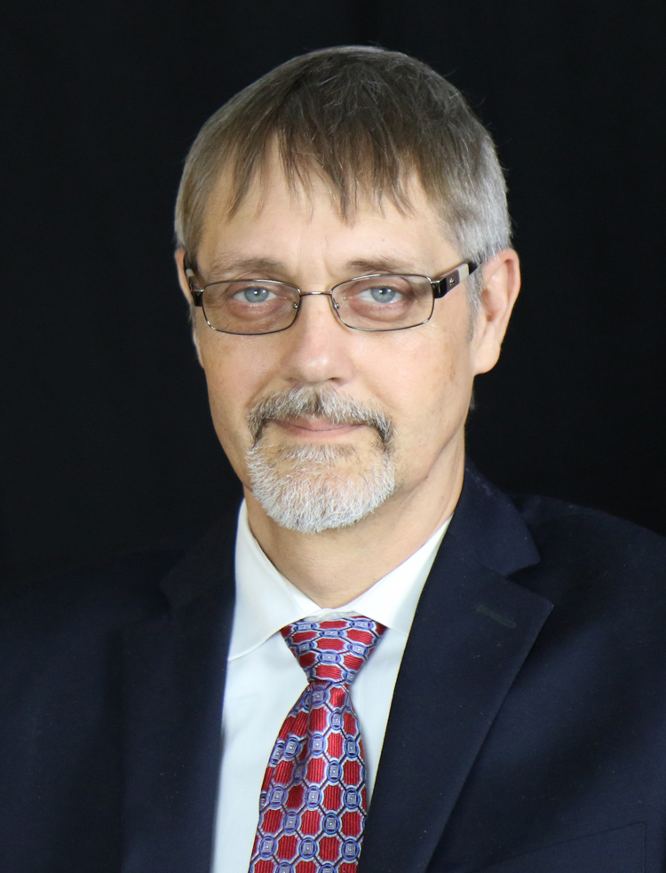 "A close-up photo of John Tschida, author of the third of the four visions of self-determination in the article ""The Future of Self-Determination: Four Visions."" He is seated, wearing a suit and tie, and looking directly at the camera and smiling."