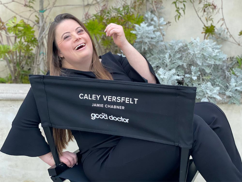 An actress on a movie set sits with her legs across a director's chair, her head tilted back as she laughs. She is white, with long, straight brown hair.