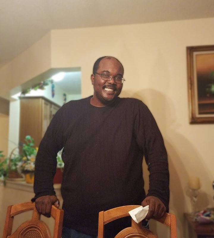A Black man wearing a brown, long-sleeved t-shirt and glasses smiles as he stands at a table. A picture hangs on the wall behind him and plants can be seen in the background.