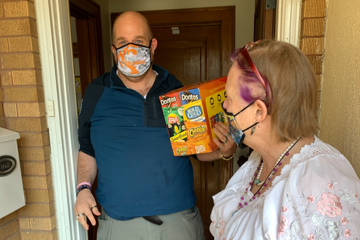 A mother delivers a box of snacks to her adult son in his group home. Both are wearing masks. The mother is turned away from the camera, looking at her son. She is wearing a white blouse. The son, wearing a blue short-sleeved shirt, looks at the camera as he holds the box of snacks.