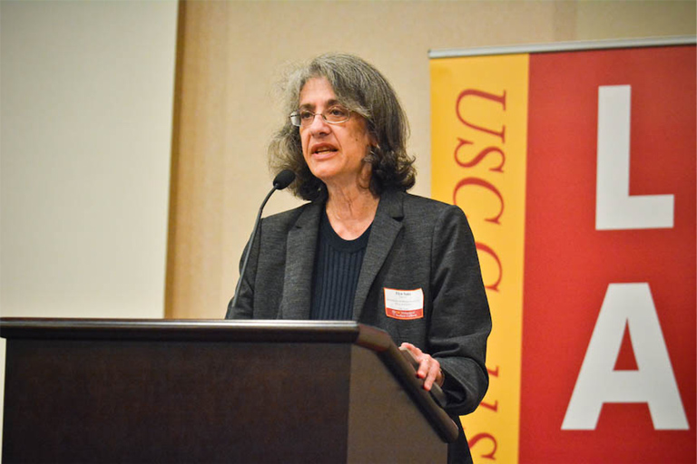 "A close-up photo of Elyn Saks, who tells her personal story in the article ""The Power of Making Decisions."" She is standing at a podium speaking to an audience in front of a large banner on the wall on which ""USC"" (meaning University of Southern California) is visible."
