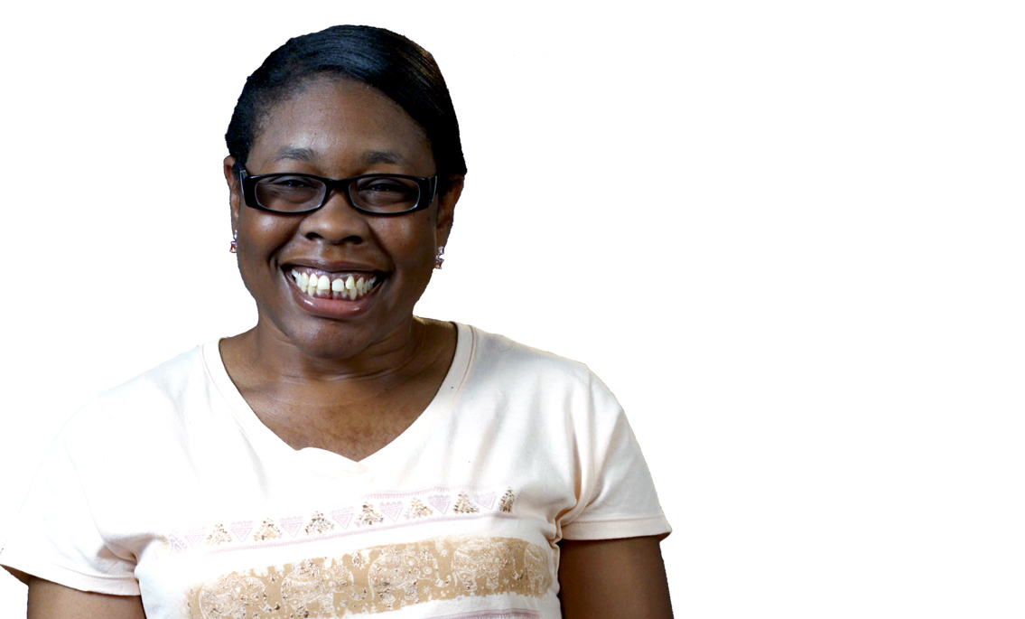 Chaqueta Stuckey, wearing glasses and smiling broadly and wearing a white t-shirt with graphic designs.