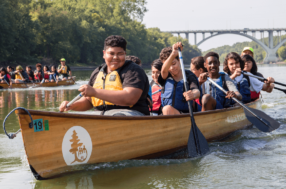 Young people from diverse background paddling a large canoe on a big river. The weather is sunny and warm.