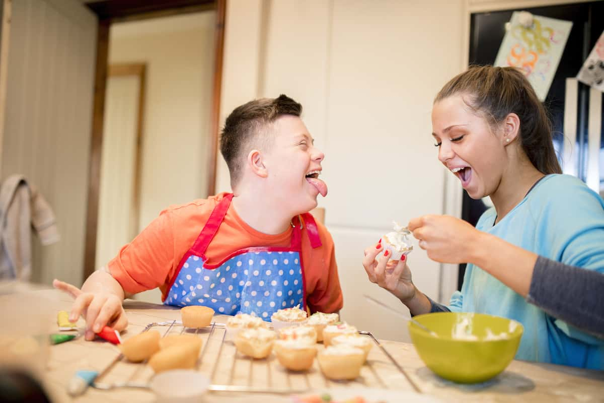 Teenage brother with Down syndrome and his sister seated at a kitchen table spreading frosting on cupcakes. He has his mouth wide open and tongue sticking out toward her as she spreads a spoonful of frosting on a cupcake, and both are laughing.