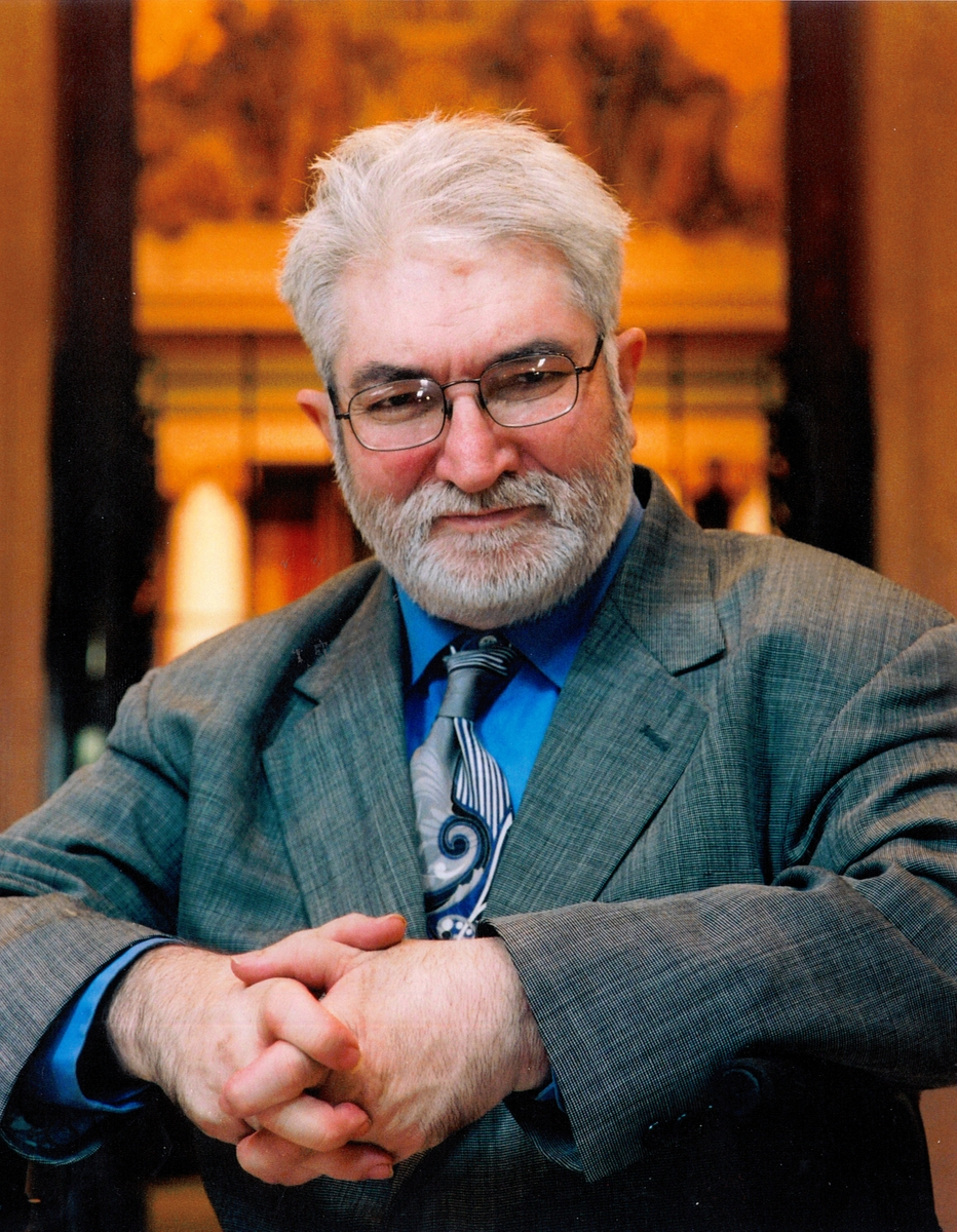 Cliff Poetz in a gray suit and tie with a blue shirt. He is wearing thin, dark-rimmed glasses and a gray beard and mustache.