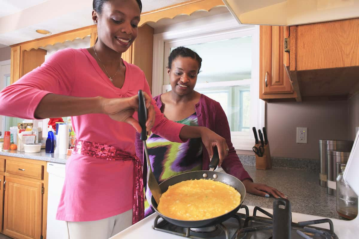Two adult sisters cooking together.