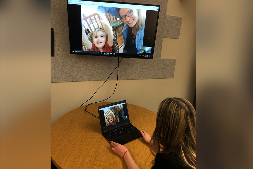 ICI's Jessica Simacek, and her young son, on screen in the Institute's Telehealth Laboratory, which she manages.
