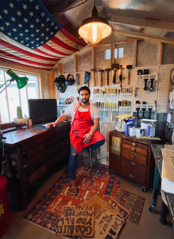 A man with a beard and mustache and wearing a red apron sits on a stool in a workshop. An American flag hangs above him, and on the wall behind him are rows of screwdrivers, hammers, and other tools.