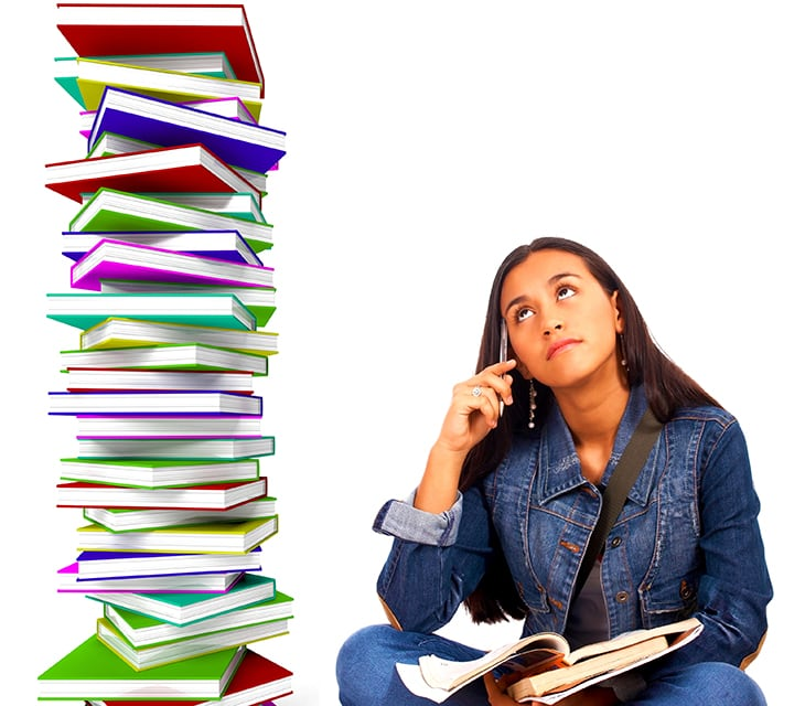 Sophia sits with a pile of schoolwork in her lap, looking up with a frown at a stack of books next to her which is taller than she is.