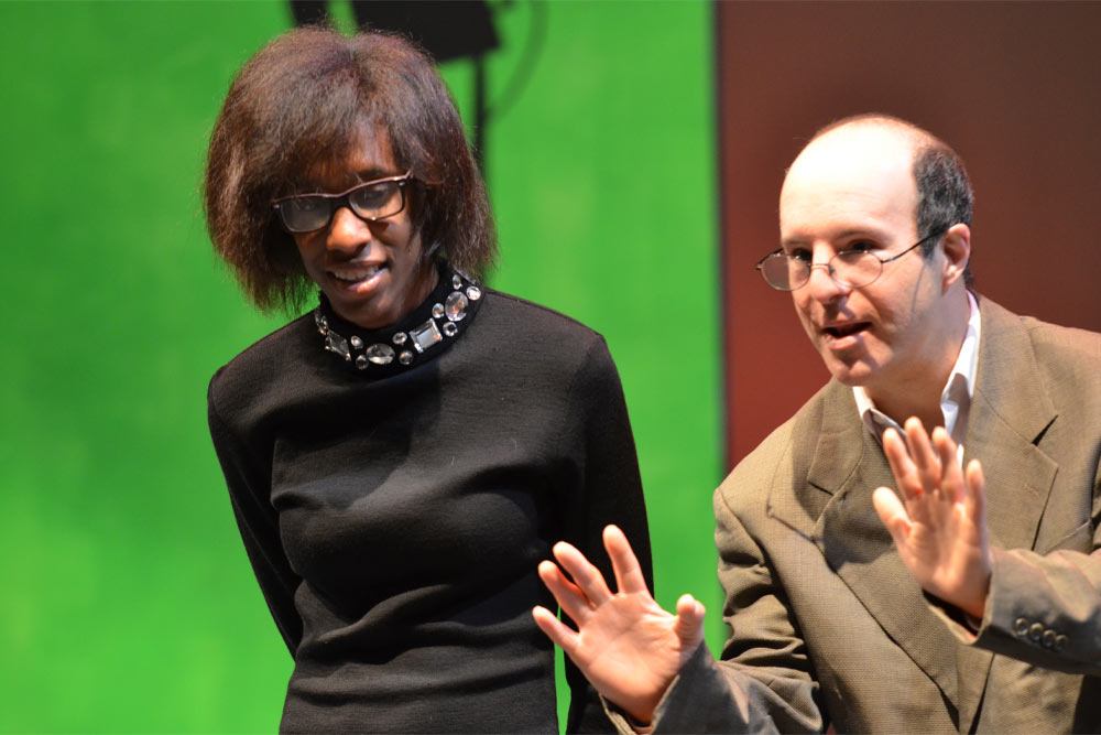 A tall, thin Black woman wearing a black shirt with gemstones in the collar and black glasses stands in front of a bright green background as a white man in a brown suit with glasses holds up his hands.