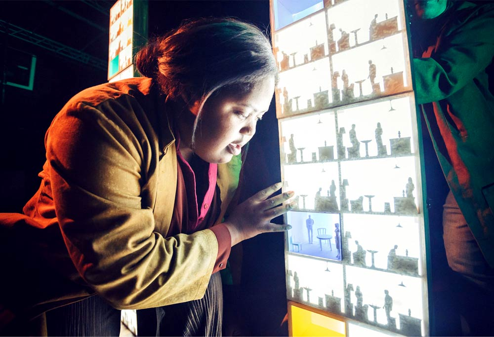A Black woman with a yellow coat and her hair tied back in a small bun leans toward a lighted, vertical panel featuring several different scenes of furniture and people.