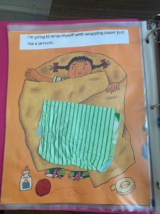 A girl wrapping herself like a present has been adapted. The image has been cut out, and a piece of wrapping paper has been added for texture. The page has been laminated and put in a three-ring binder.