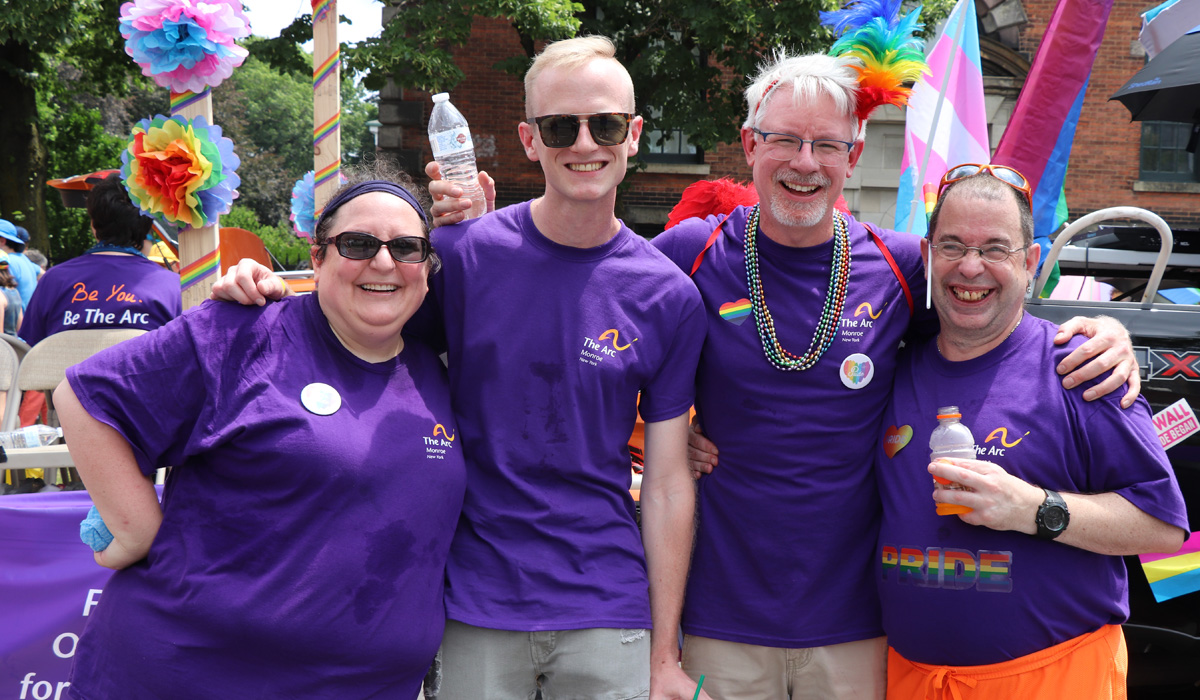 Woman and three men at Pride. They are wearing colorful purple t-shirts from The Arc of Monroe.