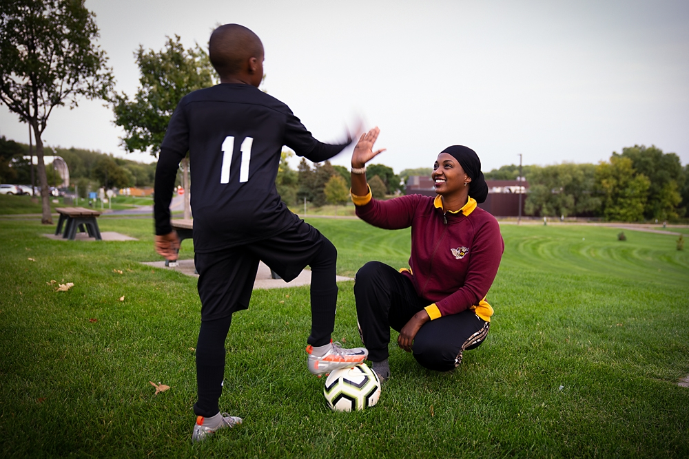 Muna Khalif (right) coaches a young soccer player.