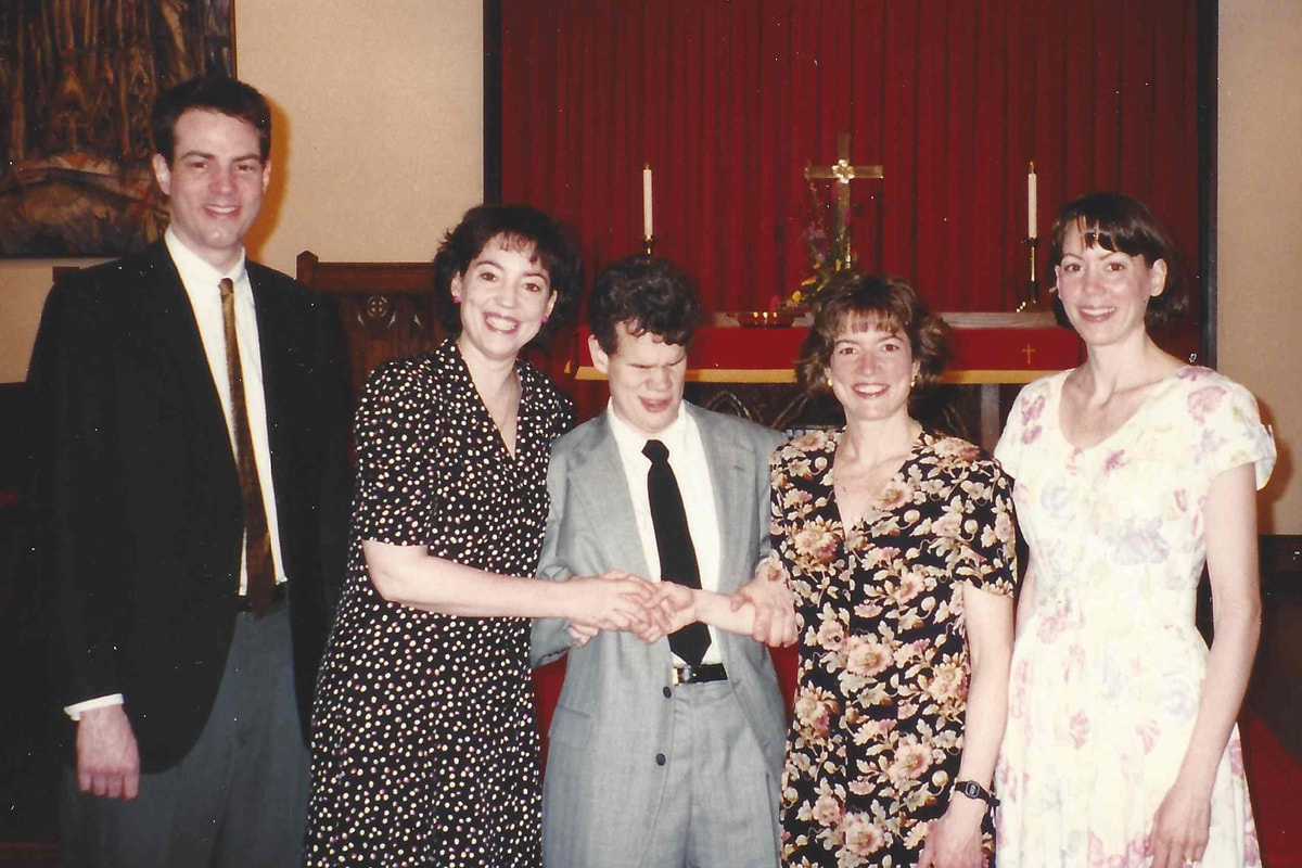 Five adult siblings stand in front of a church alter in this family photo from 1996. The two men are in suits and ties, and the three women are wearing floral-print dresses.