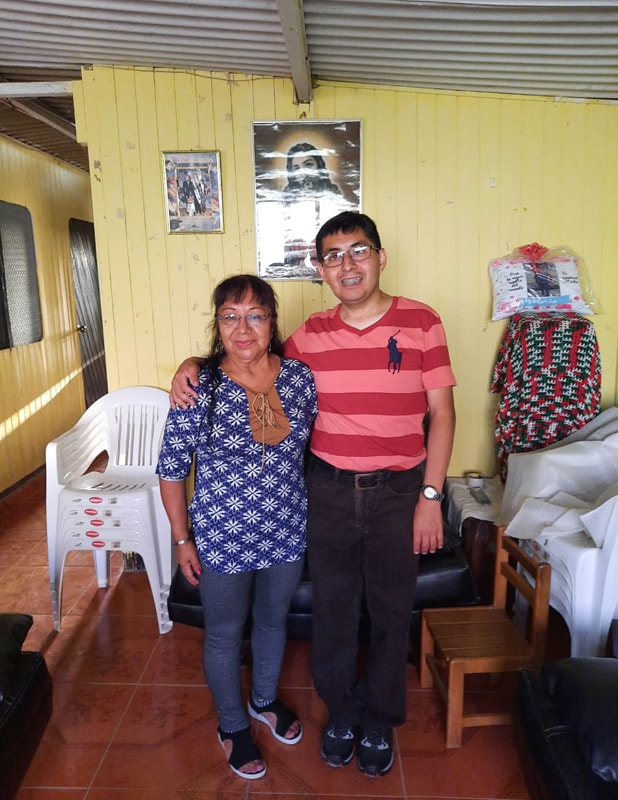 A mother stands with her adult son in their home in Peru. The son has his arm around his mother and is smiling, showing braces on his teeth. He's wearing a striped shirt that features a polo player logo. His mother wears a blue patterned dress with jeans.