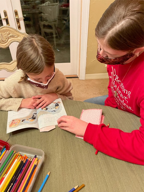 A woman wearing a mask and a red sweatshirt looks down at a young girl. The girl also wears a mask and is looking at a book on a table. Also on the table is a box of brightly colored pencils.
