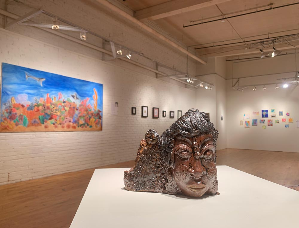 A ceramic piece featuring a face sits on a small display stand with paintings in the background during an art show.