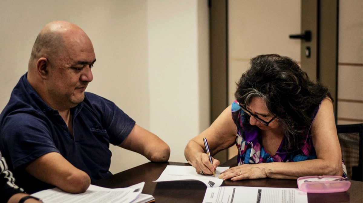 A bald, Chilean man with no hands sits at a table across from a Chilean woman with dark hair. She is wearing a print patterned top and signing a document. A pink glasses case and several papers are on the table.