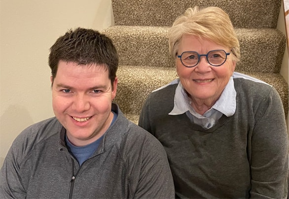 A young man with dark hair and a gray quarter-zip pullover sits on a carpeted stairway next to his mother, a woman with blonde hair and dark, round glasses.
