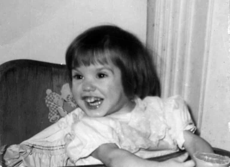 Gayle Smith as a young child in 1958, sitting in a high chair and smiling excitedly.