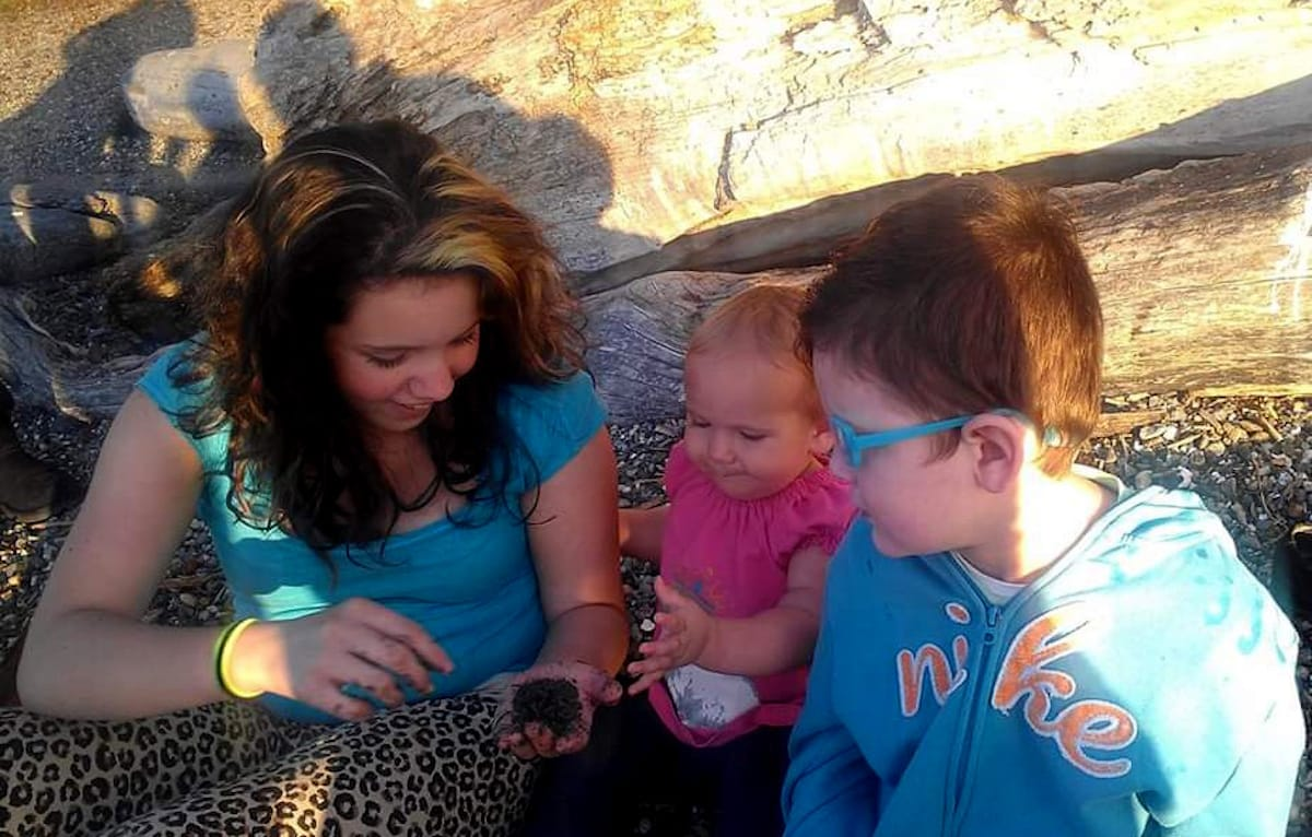 Three siblings – the adolescent sister, elementary-age brother, and baby sister – sitting on the ground next to a log looking at a handful of dirt that the older sister is holding and digging around in.