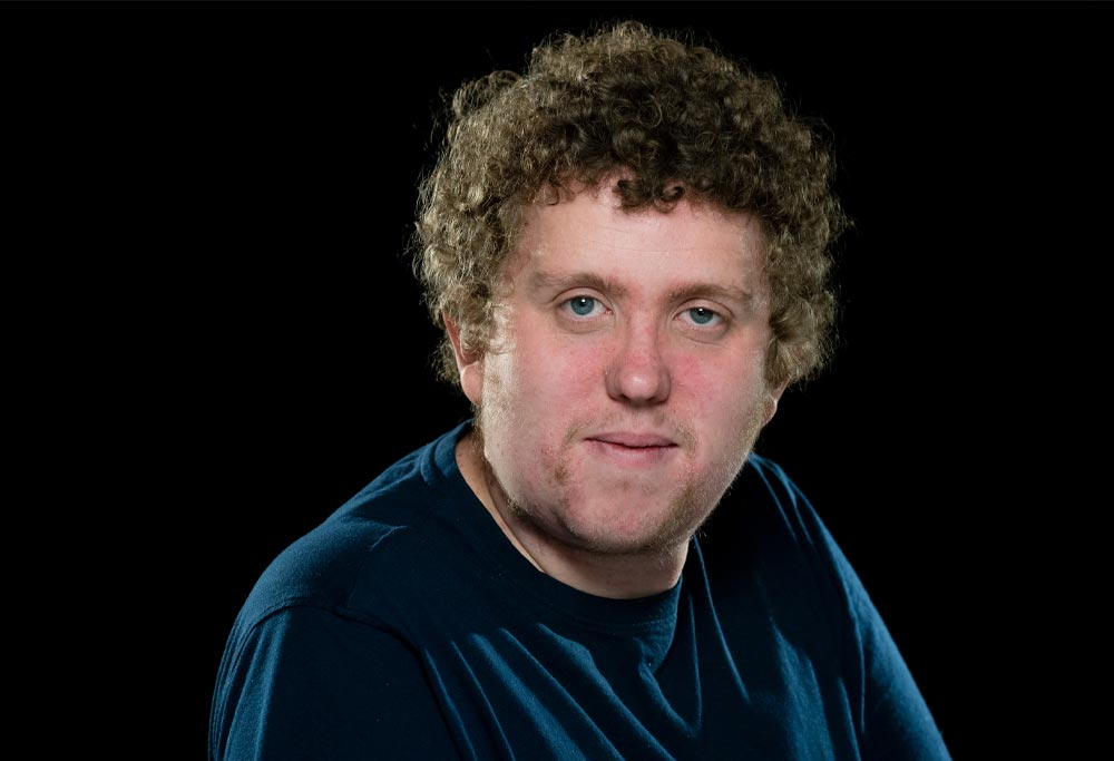 A white man with curly hair and blue eyes stares straight into the camera with a slight, closed-mount smile.