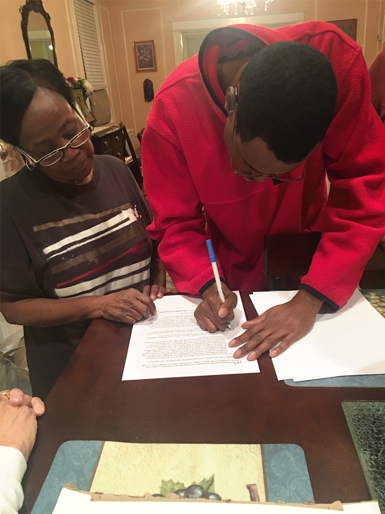 Ryan signing papers with his mother watching.