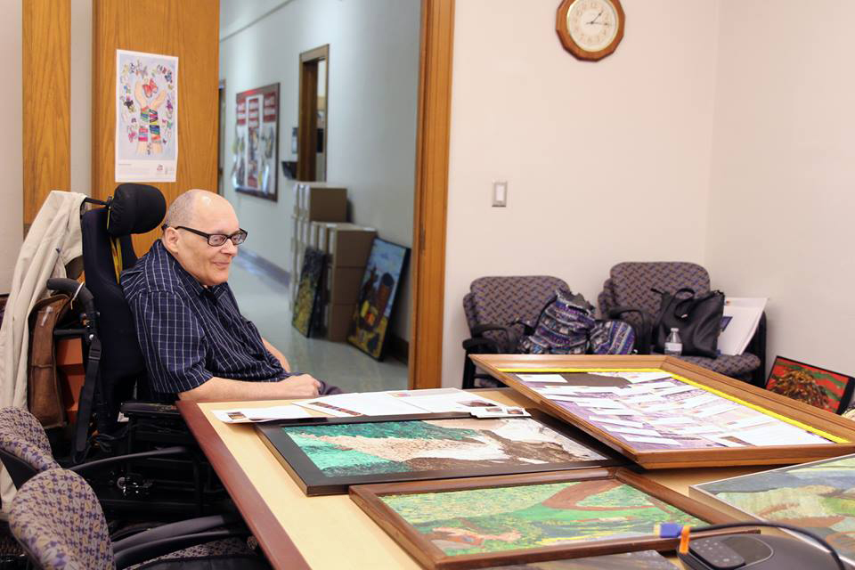 Jon Levenentz reviewing his paintings in Pattee Hall.