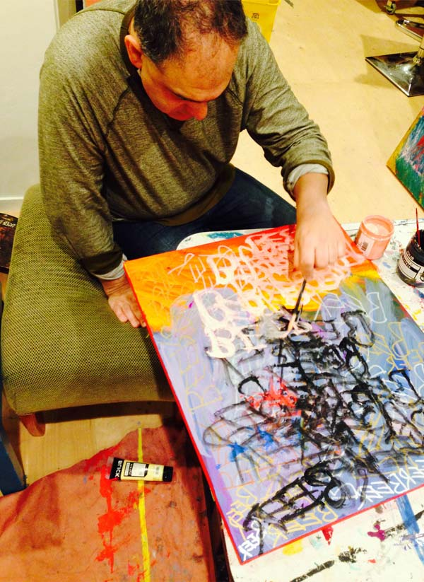 A man hunches over an abstract painting as his brush strokes the canvas.