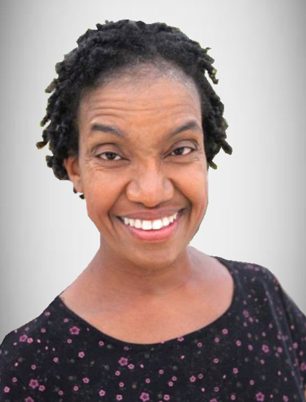 A Black woman with short hair, wearing a black floral shirt, smiles broadly and directly at the camera.