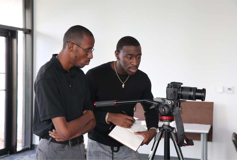 Two black men wearing black, short-sleeved shirts, look closely at a camera sitting on a tripod. One is wearing glasses, the other a gold necklace and earring.