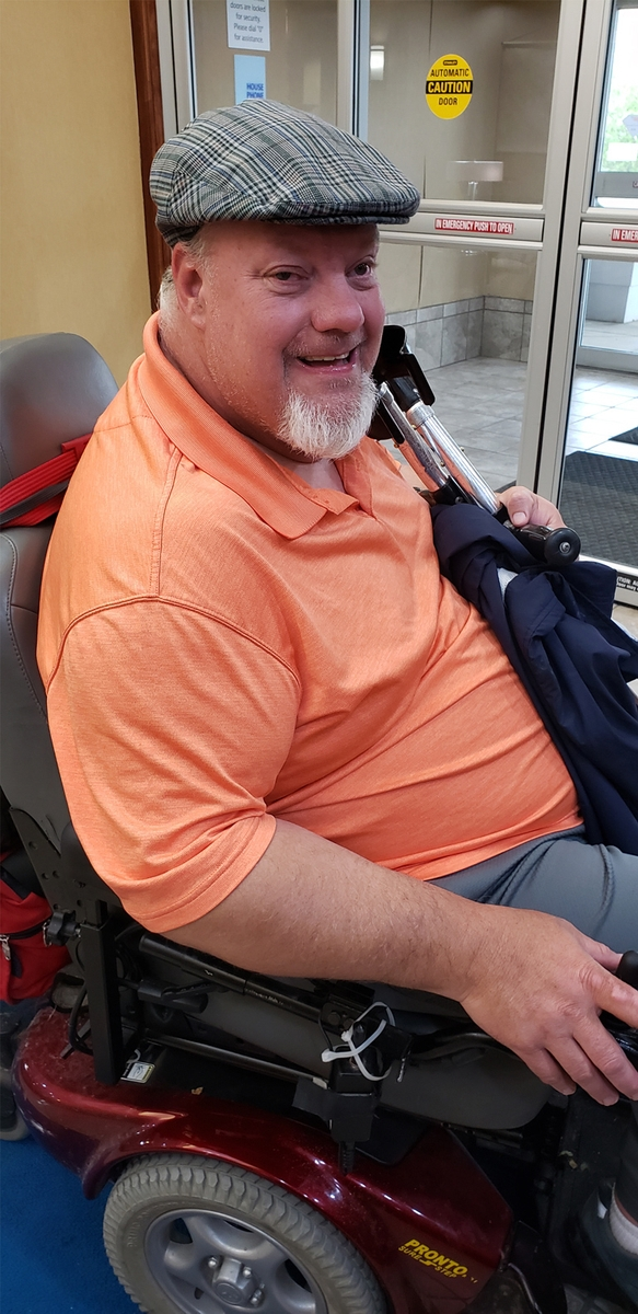 "A photo of Brad Linnenkamp, who is interviewed in this article, ""Supporting Decision-Making: Advice and Examples from a Self-Advocate."" He is sitting in a motorized wheelchair or scooter inside the sliding glass doors of a building entrance, and is looking at the camera and smiling."